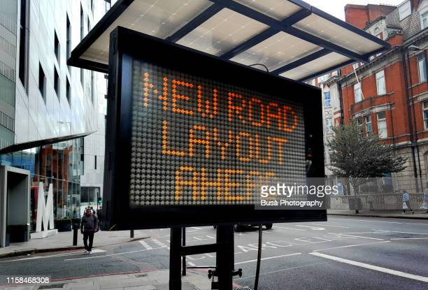 """new road layout ahead"" sign in london, uk - segnale informativo foto e immagini stock"