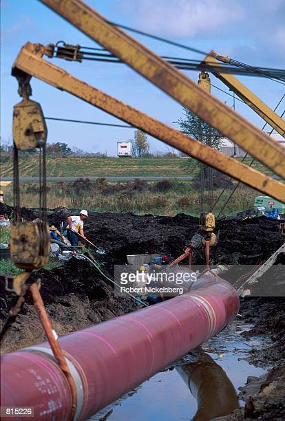 A new section of pipe is moved into position to be placed underwater in a peat bog wetland area October 4 2000 near Howell Michigan 60 miles north of...