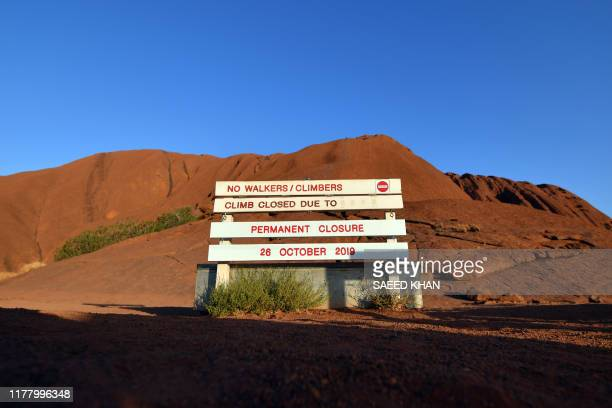 New signage marking a permanent ban on climbing Uluru, also known as Ayers Rock, is seen at the base of the monolith at Uluru-Kata Tjuta National...