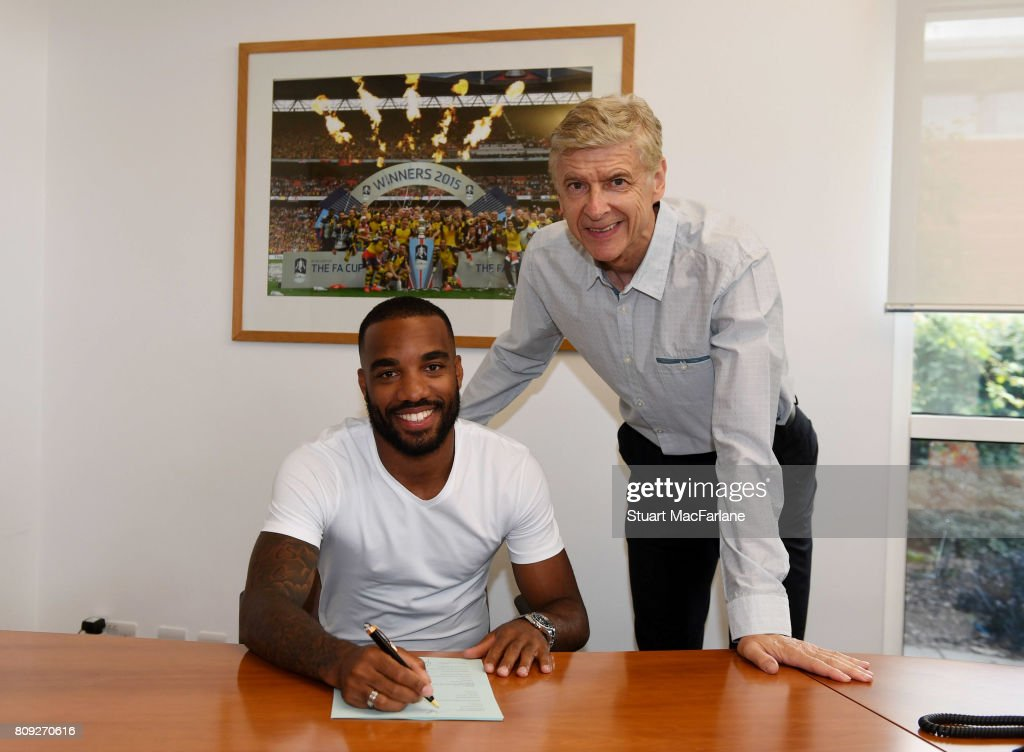 New signing Alexandre Lacazette signs his contract with Arsenal manager Arsene Wenger at London Colney on July 4, 2017 in St Albans, England.