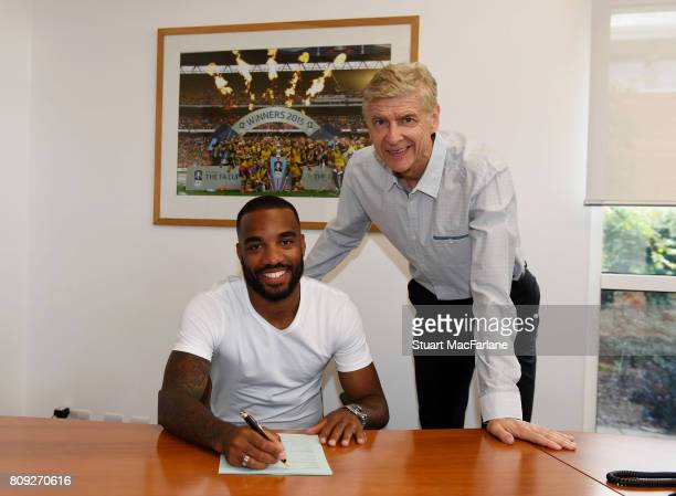 New signing Alexandre Lacazette signs his contract with Arsenal manager Arsene Wenger at London Colney on July 4 2017 in St Albans England