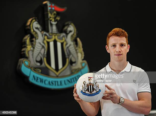 New signing Jack Colback poses for photographs whilst holding a Newcastle football in front of the club crest at St.James' Park on June 9, 2014 in...
