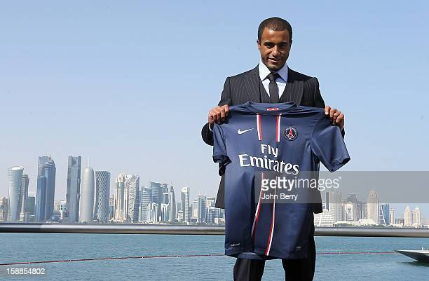 New signing Lucas Moura of PSG poses with a shirt as he is officially unveiled as a player of Paris Saint-Germain during a press conference and...