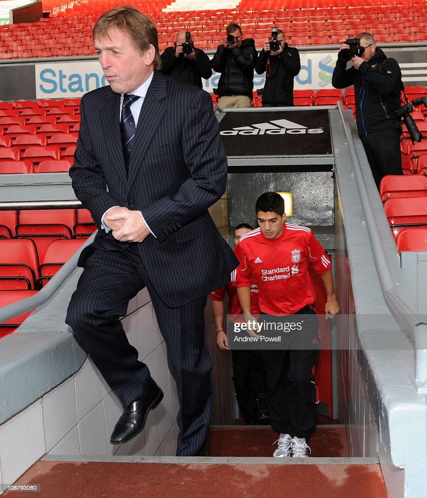 New signing Luis Suarez of Liverpool and manager Kenny Dalglish walk out from the tunnel to pose for photographers at Anfield on February 3, 2011 in Liverpool, England.