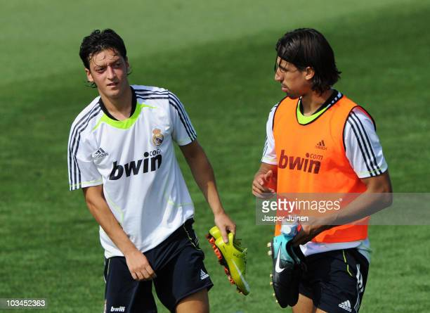 New signing Mesut Ozil of Real Madrid chats with his fellow countryman Sami Khedira at the end of a training session at the Valdebebas training...