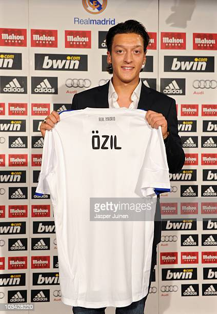 New signing Mesut Ozil poses with a Real Madrid shirt during his presentation as new Real Madrid player at the Estadio Santiago Bernabeu on August...