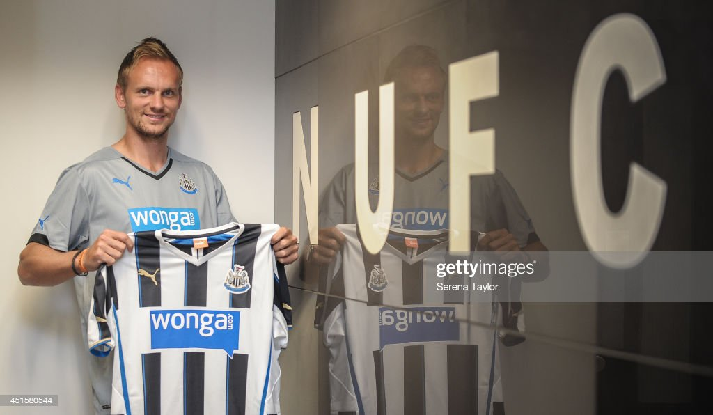 New signing Siem de Jong poses for photographs holding a Newcastle shirt in the home team dressing room at St.James' Park on July 01, 2014 in Newcastle upon Tyne, England.