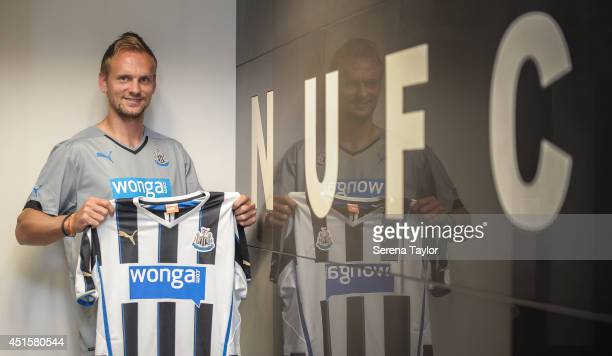 New signing Siem de Jong poses for photographs holding a Newcastle shirt in the home team dressing room at St.James' Park on July 01, 2014 in...