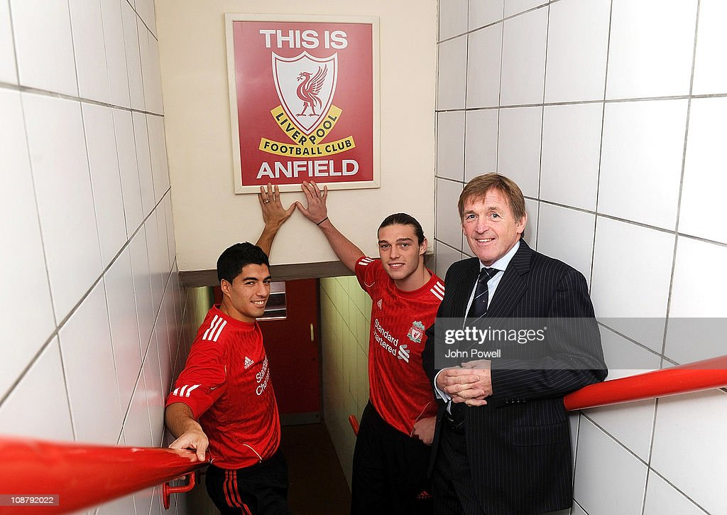 New signings Andy Carroll (C) and Luis Suarez (L) of Liverpool pose for a photograph in their shirts as they touch the This is Anfield sign next to manager Kenny Dalglish at Anfield on February 3, 2011 in Liverpool, England.