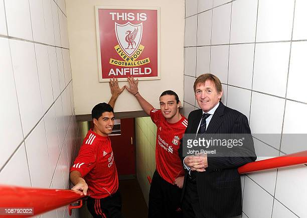 New signings Andy Carroll and Luis Suarez of Liverpool pose for a photograph in their shirts as they touch the This is Anfield sign next to manager...