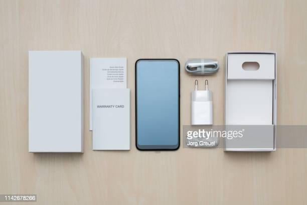 new smartphone with packaging and accessories - unboxing stock pictures, royalty-free photos & images