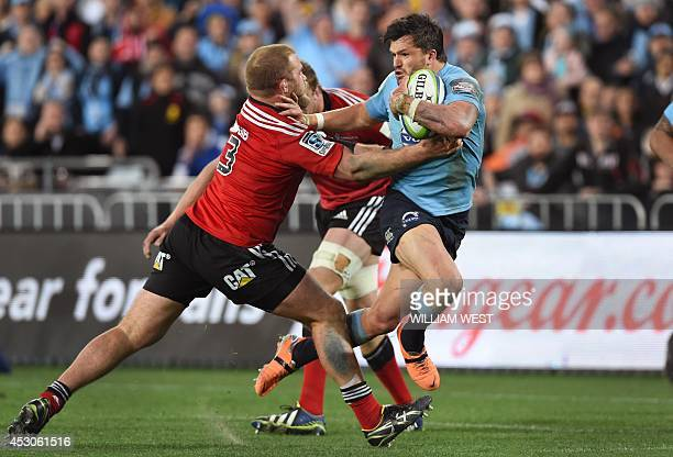 New South Wales Waratahs centre Adam AshleyCooper pushes off the tackle of Canterbury Crusaders prop Owen Franks to score during the Super 15 rugby...