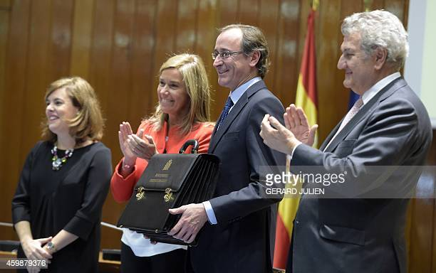New Spanish Health Social Services and Equality Minister Alfonso Alonso holds the briefcase of newly appointed minister as he poses with Deputy Prime...