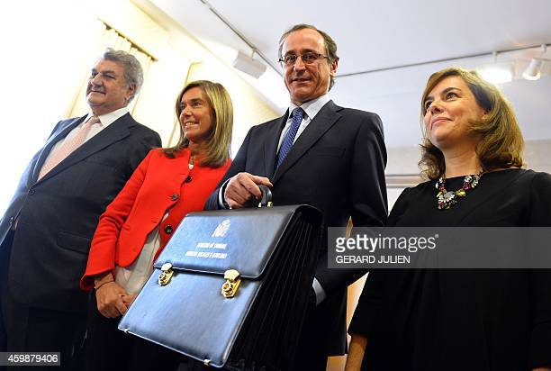 New Spanish Health Social Services and Equality Minister Alfonso Alonso holds the briefcase of newly appointed minister as he poses with President of...