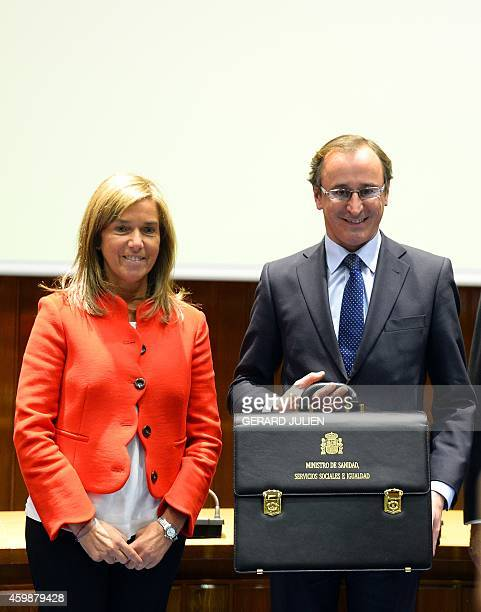 New Spanish Health Social Services and Equality Minister Alfonso Alonso holds the briefcase of newly appointed minister as he poses with former...