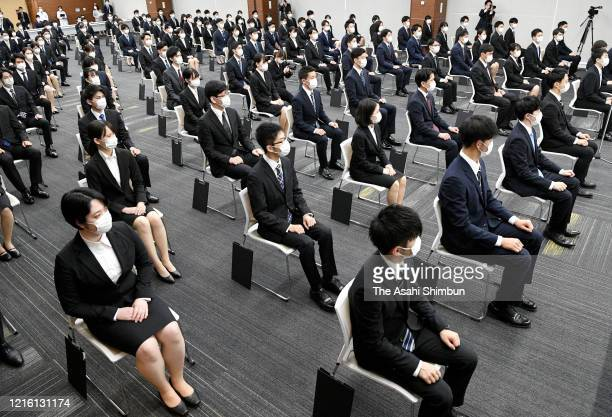 New staffs wearing face masks sit with distance during the welcome ceremony of the NishiNippon City Bank amid the novel coronavirus pandemic on April...