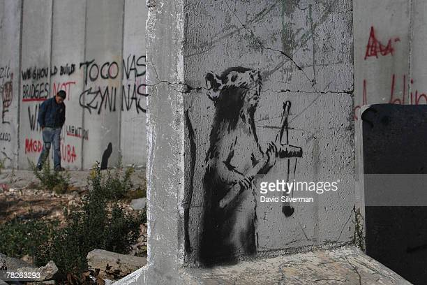 A new stencil painting on a concrete barricade by elusive British graffiti artist Banksy shows a rat holding a slingshot December 5 2007 opposite an...