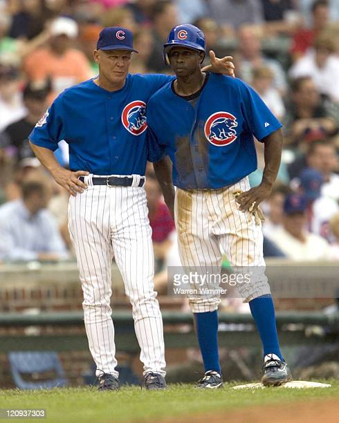 New third base coach, Mike Quade of the Chicago Cubs, confers with Juan Pierre, after Pierre just stole third base during game action at Wrigley...