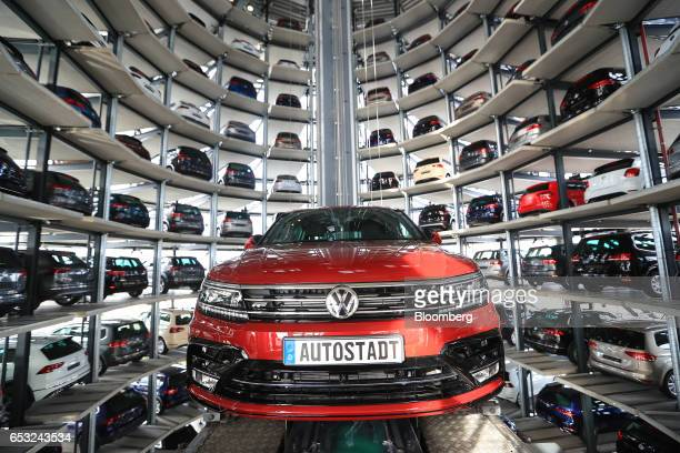 A new Tiguan sports utility vehicle produced by Volkswagen AG is transported on an elevation platform as new VW automobiles sit in storage bays...