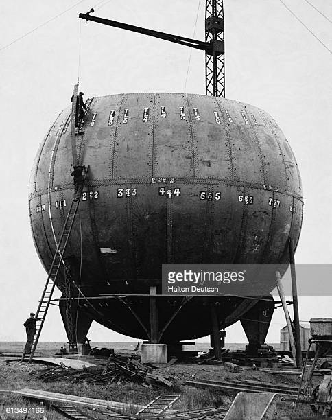 A new type of gas storage tank under construction on Canvay Island Four pillars support a round balloonlike structure | Location Canvay Island Essex...