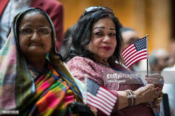 New United States citizens Khanom Hazera and Milagros Altagracia hold American flags during a naturalization ceremony at the New York Public Library...