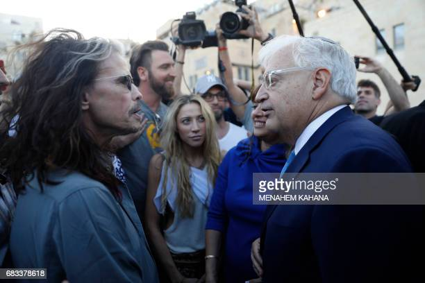 New US ambassador to Israel David Friedman talks with US band Aerosmith's lead singer Steven Tyler after the two met by coincidence following a visit...