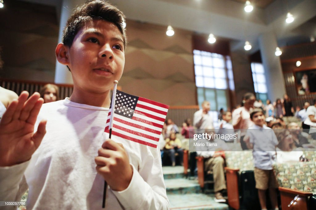 New U.S. citizen Davies Garcia, 11, originally from Mexico, holds an American flag during a naturalization ceremony conducted by U.S. Citizenship and Immigration Services (USCIS), on September 14, 2018 in Los Angeles, California. USCIS presented citizenship papers at the L.A. Public Library to around 50 young people who obtained their citizenship via their parents. Some of the young people became citizens once their immigrant parents became citizens while others were adopted by citizens of the U.S. The ceremony was part of annual Constitution Week and Citizenship Day celebrations conducted by USCIS.