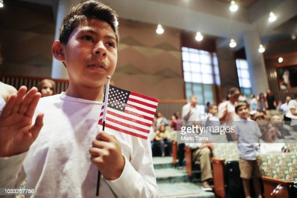 New US citizen Davies Garcia originally from Mexico holds an American flag during a naturalization ceremony conducted by US Citizenship and...