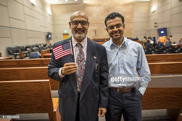 A new US citizen left holds an American flag while standing for a photograph with his son during a naturalization ceremony at the Evo A DeConcini US...