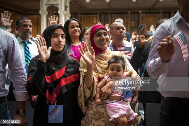 New US citizen Mosammat Rasheda Akter orginally Bangladesh holds her 7 monthold daughter Fahmida as she recites the Oath of Allegiance during...