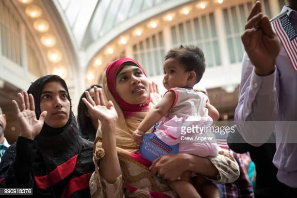New US citizen Mosammat Rasheda Akter orginally Bangladesh holds her 7 monthold daughter Fahmida as she recites the Oath of Allegiance during...