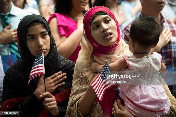 New US citizen Mosammat Rasheda Akter orginally Bangladesh holds her 7 monthold daughter Fahmida as she sings the US National Anthem during...