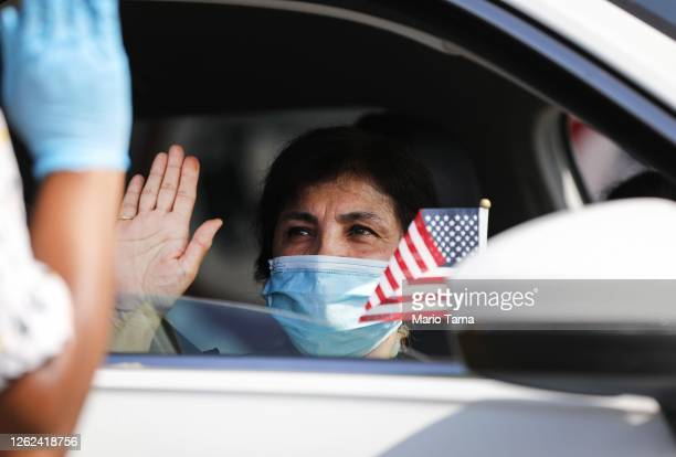 New U.S. Citizen sits in a vehicle while being sworn in by an immigration service officer at a drive-in naturalization ceremony amid the COVID-19...