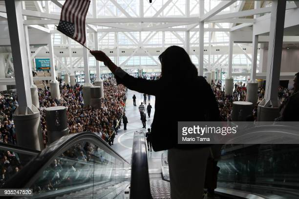 A new US citizen waves an American flag while departing a naturalization ceremony on March 20 2018 in Los Angeles California The naturalization...