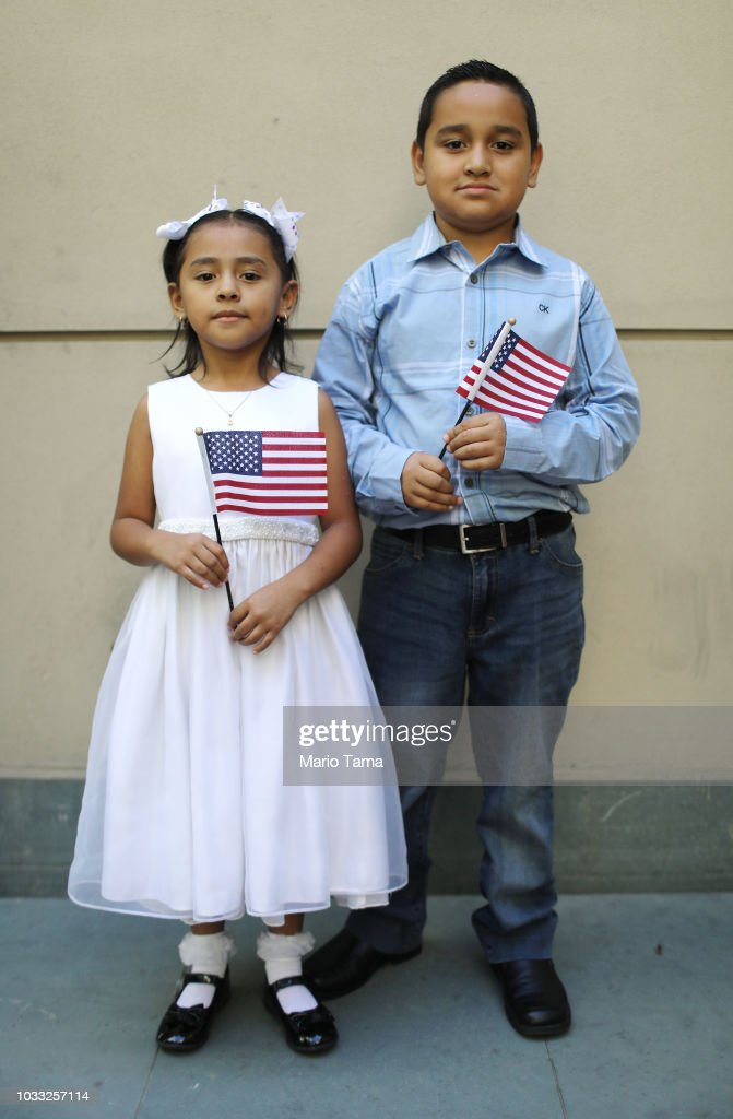 New U.S. citizens Alexa Ayala Salgado and her brother Edgar, originally from Mexico, pose holding American flags following a naturalization ceremony conducted by U.S. Citizenship and Immigration Services (USCIS), on September 14, 2018 in Los Angeles, California. USCIS presented citizenship papers at the L.A. Public Library to around 50 young people who obtained their citizenship via their parents. Some of the young people became citizens once their immigrant parents became citizens while others were adopted by citizens of the U.S. The ceremony was part of annual Constitution Week and Citizenship Day celebrations conducted by USCIS.