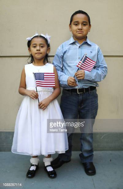 New US citizens Alexa Ayala Salgado and her brother Edgar originally from Mexico pose holding American flags following a naturalization ceremony...