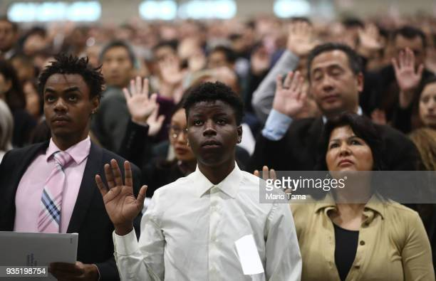 New US citizens James Maina from Kenya and Esther Ranfla from Mexico take the citizenship oath along with other new citizens at a naturalization...