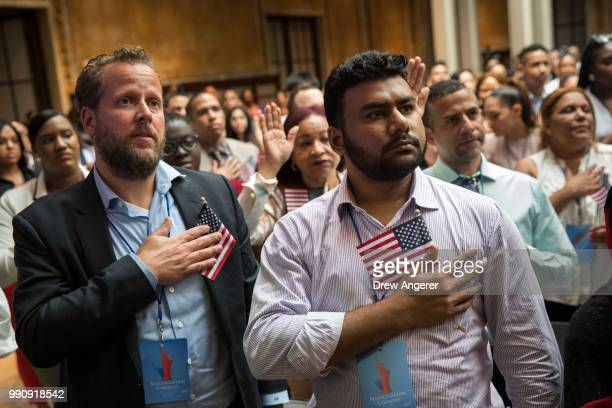 New U.S. Citizens recite the Pledge of Allegiance during naturalization ceremony at the New York Public Library, July 3, 2018 in New York City. 200...