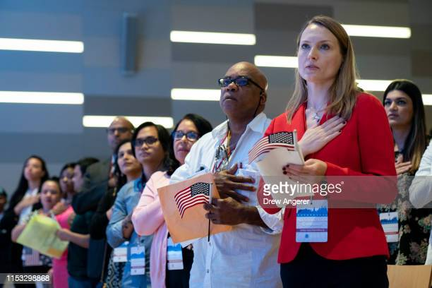 New U.S. Citizens stand for the Pledge of Allegiance during a naturalization ceremony inside the National September 11 Memorial Museum on July 2,...