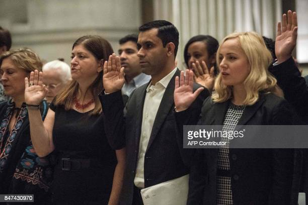 New US citizens take the oath of citizenship at a naturalization ceremony at the National Archives in Washington DC on September 15 2017 / AFP PHOTO...