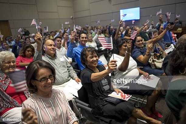 New US citizens wave American flags during a naturalization ceremony at the Evo A DeConcini US Courthouse in Tucson Arizona US on Friday Sept 16 2016...