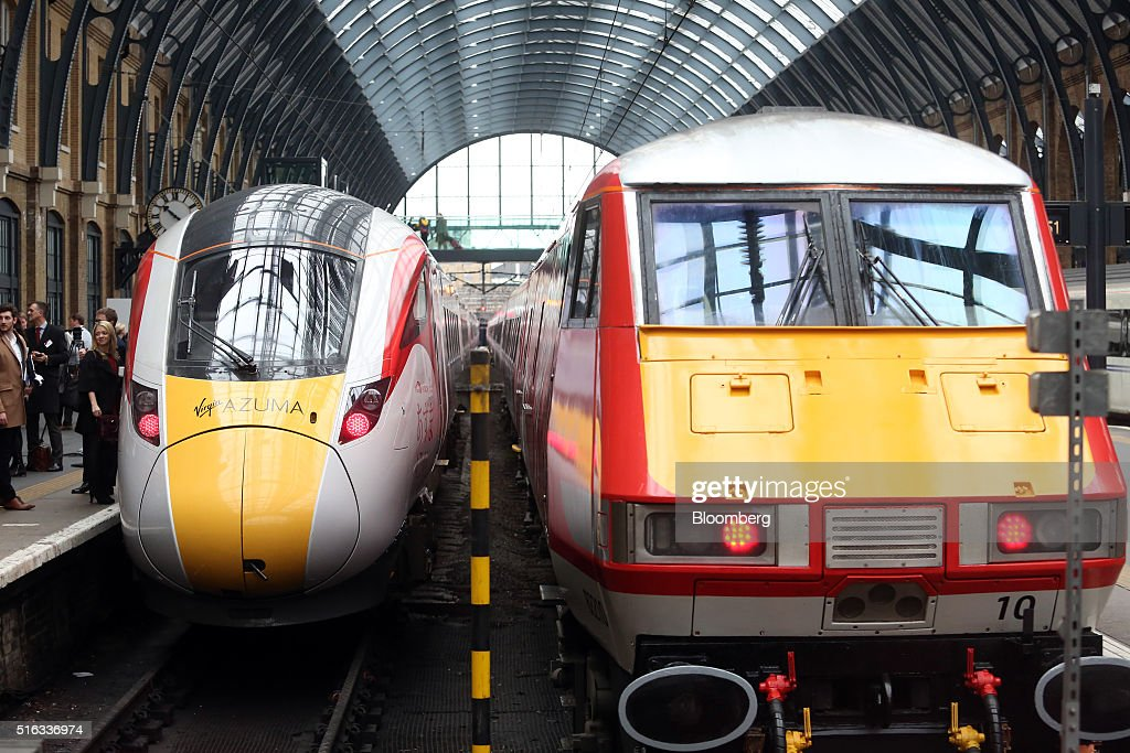 A new Virgin Azuma high speed train, manufactured by Hitachi Ltd., left, stands at a platform at Kings Cross station, London, U.K., on Friday, March 18, 2016. Virgin Trains will revive plans to offer high-speed Internet access on Europes busiest rail route in a bid to beat the plane and persuade business people to travel outside peak hours. Photographer: Chris Ratcliffe/Bloomberg via Getty Images