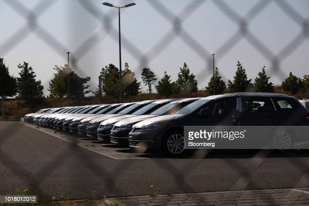 New Volkswagen AG automobiles sit stockpiled behind a fence in a parking lot at Willy Brandt Berlin Brandenburg International Airport in Schoenefeld...