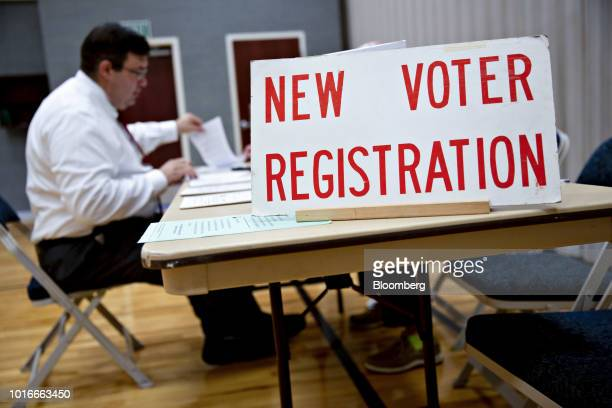 A New Voter Registration sign sits on a table at a polling station in Janesville Wisconsin US on Tuesday Aug 14 2018 The Wisconsin primary will set...