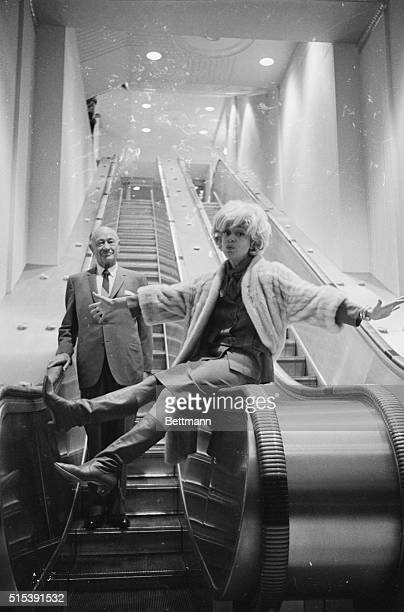 New Waldorf-Astoria Escalator. New York: Perched on rail, comedienne Carol Channing gets a big kick out of ride as she and Conrad N. Hilton,...