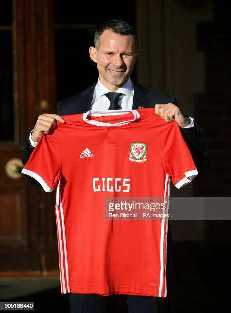 New Wales manager Ryan Giggs poses with a Wales shirt after a press conference at Hensol Caste Vale Resort Hensol