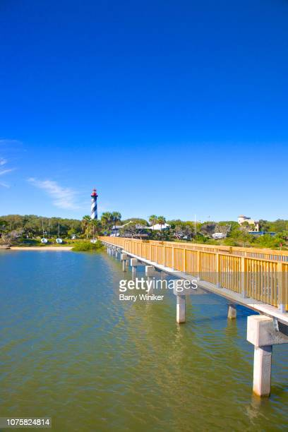 new wood pier and old lighthouse in st. augustine beach - st augustine lighthouse stock photos and pictures