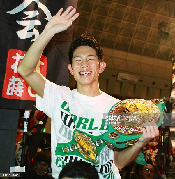 New World Boxing Council strawweight Champion Kazuo Ioka of Japan holds the champion belt waves to supporters after beating Oleydong Sithsanerchai of...