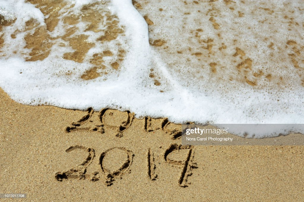 New Year 2019 and Year 2018 Written on Sandy Beach with Waves : Stock Photo