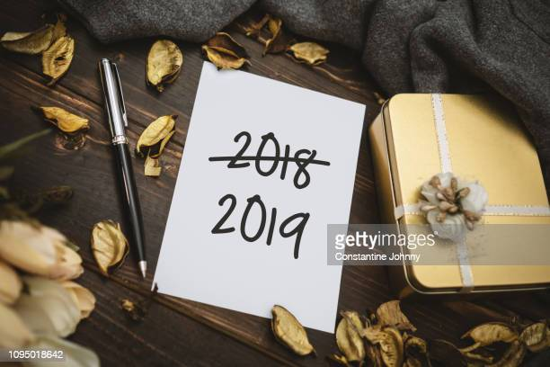 New Year 2019 Written on White Paper and 2018 on Rustic Wood Background. 2018 Crossed Out.